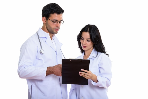 Young man and woman doctor reading on clipboard t