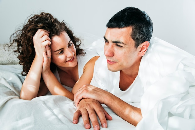 Young man and woman under duvet lying on bed