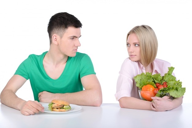 Young man and woman eating fast food.