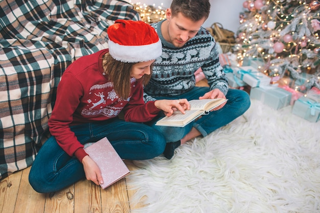 Young man and woman in festive clothes sitting on floor with legs crossed. they read book together. man has it on nap. young woman hold another book with hand. they are concentrated.
