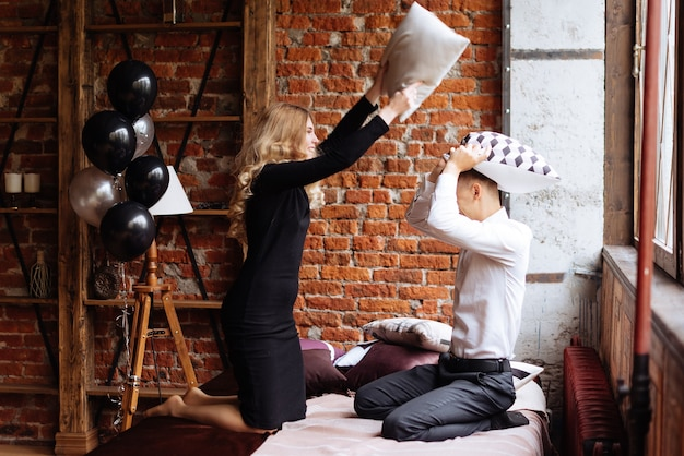 A young man and a woman fight with pillows on a bed in a loft-style room