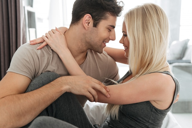Young man and woman flirting and hugging in bed