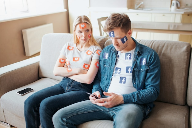 Young man and woman have social media addiction. concept of addictiveness from smartphones. angry woman on sofa.