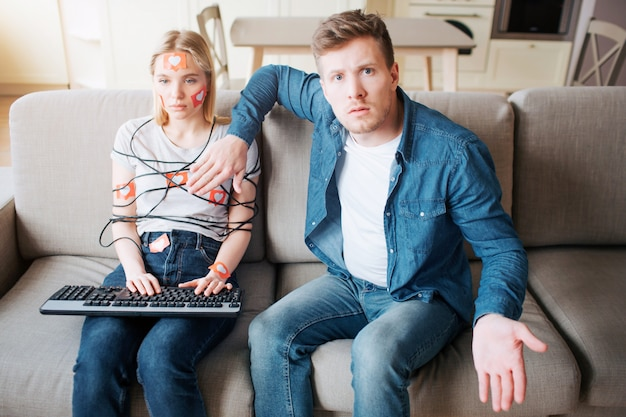 Young man and woman have social media addiction. sitting on sofa. hostages. emotionless woman on sofa. worried man looking on camera. distracted.