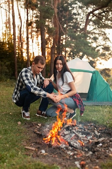 Young man and woman having a bonfire outdoors