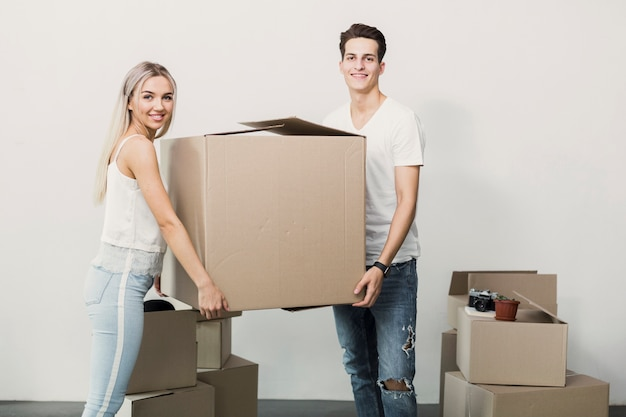 Young man and woman holding cardboard box