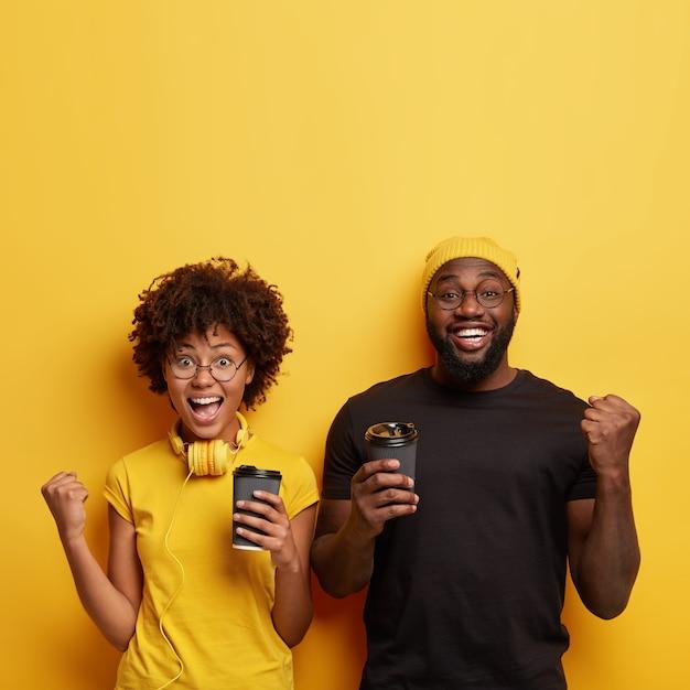 Giovane e donna che tengono le tazze di caffè