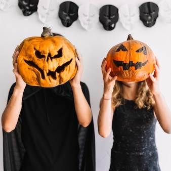 Young man and woman holding pumpkins before heads