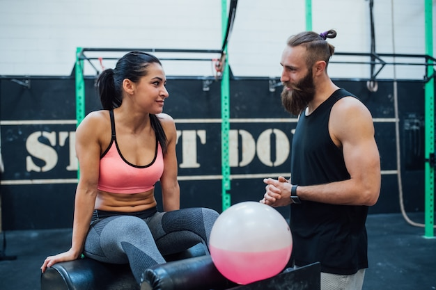 Young man and woman indoor gym relaxing taking a break