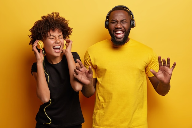 Young man and woman listening to music in headphones
