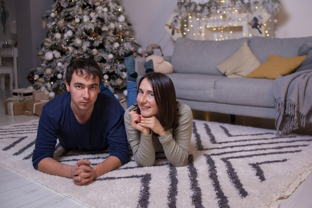 Young man and woman lying on floor near sofa and christmas tree with presents and looking at camera.