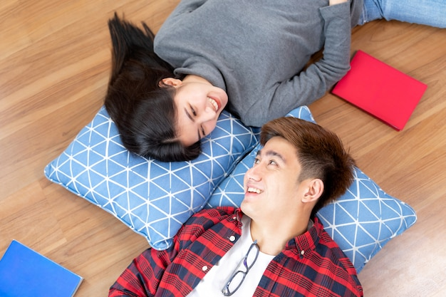 Young man and woman lying on floor and talking together