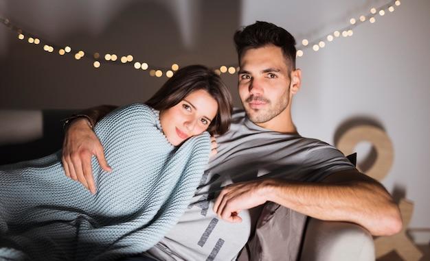 Young man and woman lying on sofa