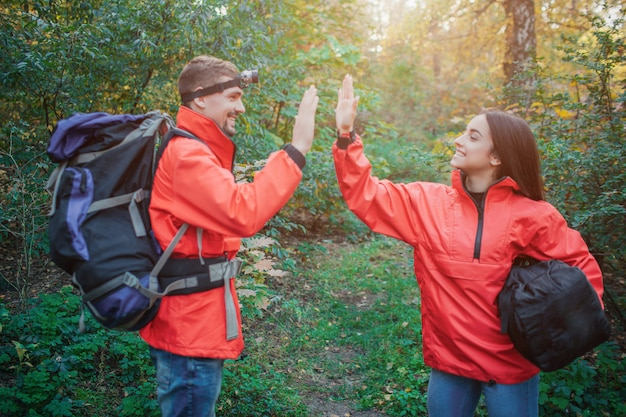 Young man and woman in orange jackets giving five sign to each other. he has backpack. she holds sleeping bag. they smile to each other. people are in forest.