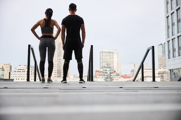 Young man and woman in outfit are standing together and looking at urban scenery after workout