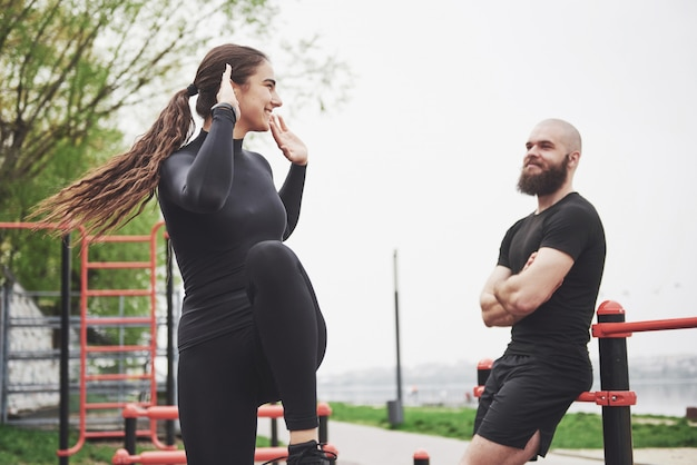 Young man and woman perform exercises and stretch marks before doing sports
