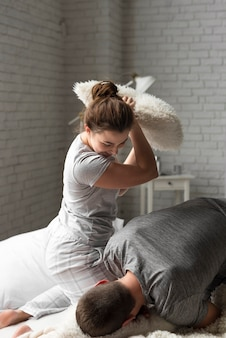 Young man and woman pillow fighting indoors
