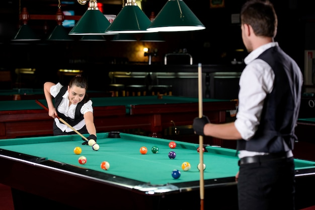 Young man and woman playing professional billiards.