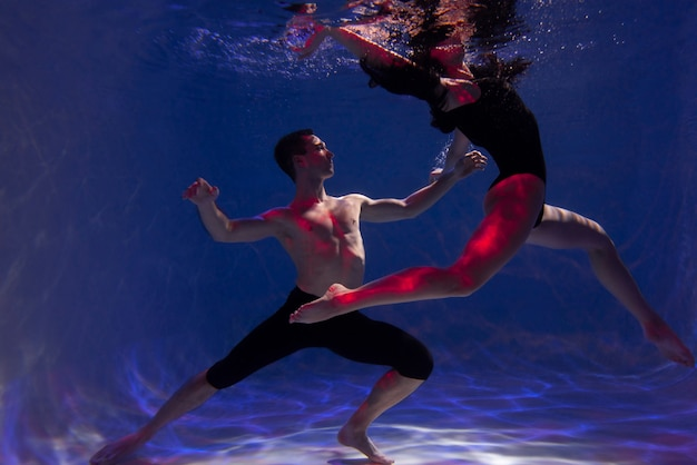 Young man and woman posing together while submerged underwater
