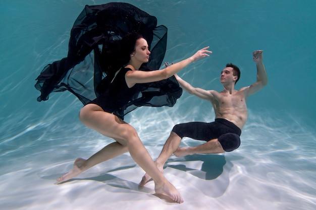 Giovane uomo e donna in posa insieme mentre sono immersi sott'acqua