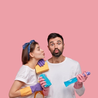 Young man and woman posing with cleaning products