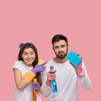 Giovane uomo e donna in posa con prodotti per la pulizia