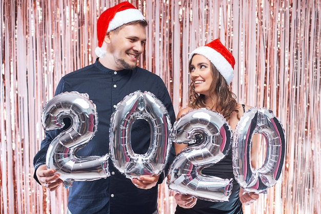 Young man and woman in red santa hats having fun with 2020 metallic balloons.