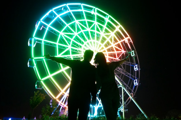 A young man and woman romance love in the night in amusement park near ferris wheel