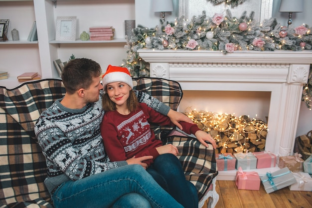 Young man and woman sit on sofa and embrace and look at each other. woman wears christmas hat. they sit at fireplace. room is decorated.