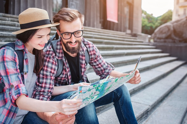 Young man and woman sit on steps outside. they hold map together. tourists smile. they look at map. travellers have rest.