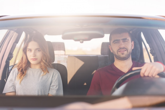 Young man and woman sitting in car