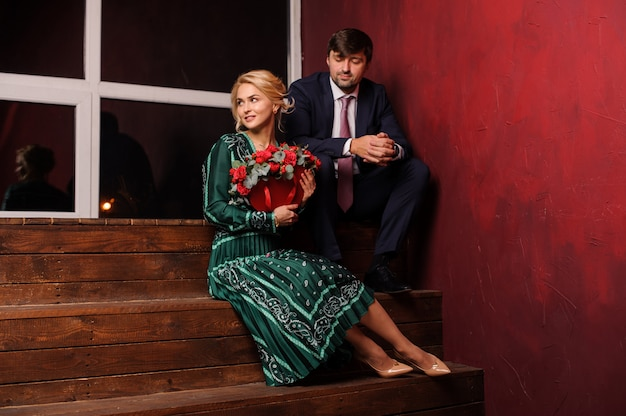 Young man and woman sitting on the stairs holding the bouquet of adorable flowers