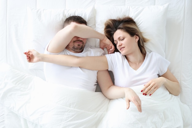 Young man and woman sleeping in large white bed