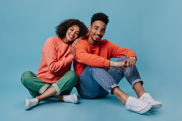 Young man and woman smiling and sitting on blue wall