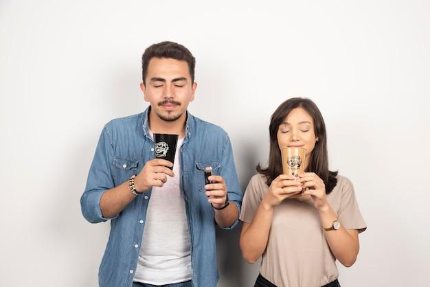 Il giovane e la donna annusa il caffè dell'aroma dalle tazze.
