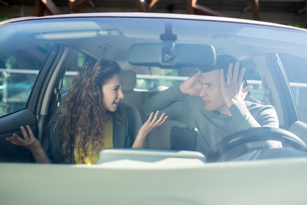Young man and woman sorting out relationships in a car
