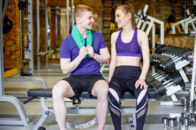Young man and woman in sportswear in the gym resting after training