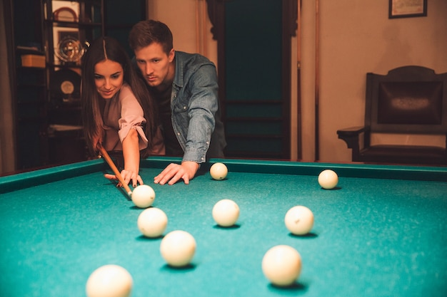 Young man and woman stand together in billiard room. he teach her how to aim into billiard ball. they dating.