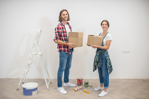 Young man and woman standing near the wall with boxes in hands