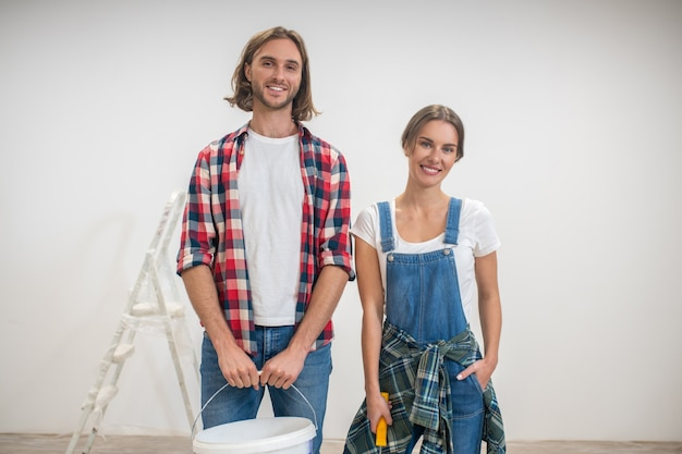 Young man and woman standing near the white wall