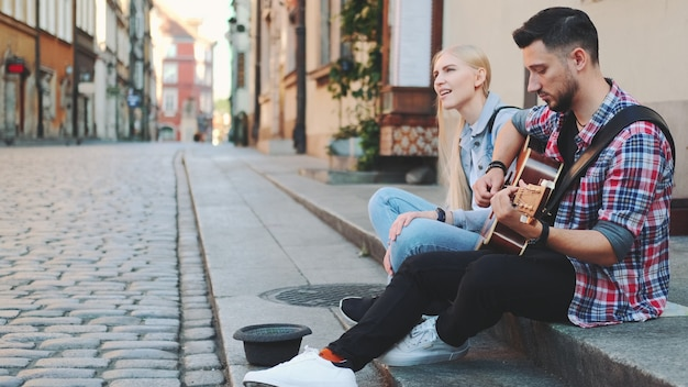 Young man and woman of street singers sitting on sidewalk, playing guitar and singing. lifestyle concept.