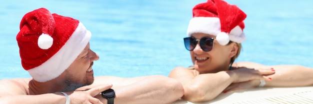 Young man and woman in sunglasses and santa claus hats talking in swimming pool