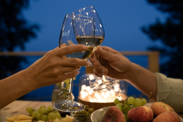 Young man and woman toasting over served table during romantic dinner