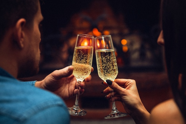 Young man and woman touchgin glasses with champagne. they look at each other. couple sit at fireplace.