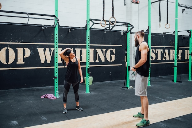 Young man and woman training together indoor gym
