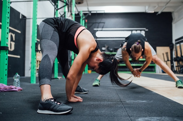Young man and woman training toghether indoor gym
