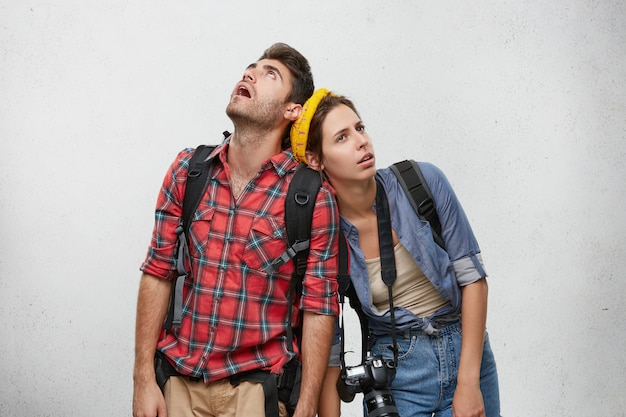 Young man and woman travelers in sensible clothes carrying heavy backpacks leaning on each other, feeling exhausted and thirsty while hiking. travel, peolple and relationships concept
