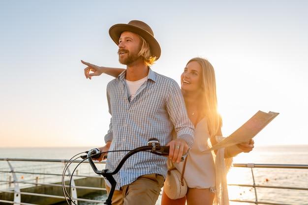 Giovane uomo e donna che viaggiano su biciclette tenendo la mappa