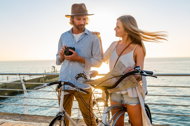 Young man and woman traveling on bicycles holding map