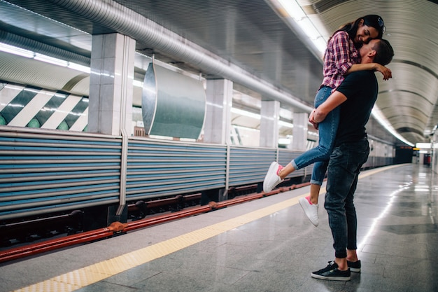 Young man and woman use underground. couple in subway. cheerful picture of young man holding woman in hands. she smile. happy together. love sotry. underground modern urban view.